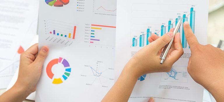 duas pessoas analisando os dados em duas folhas com vários gráficos e dados