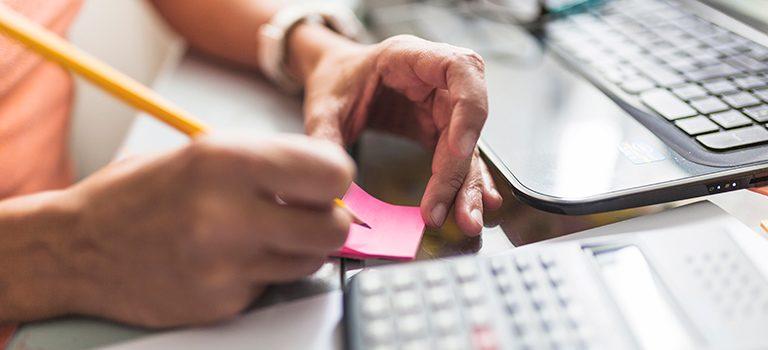 mulher anotando informações relevantes em um post-it