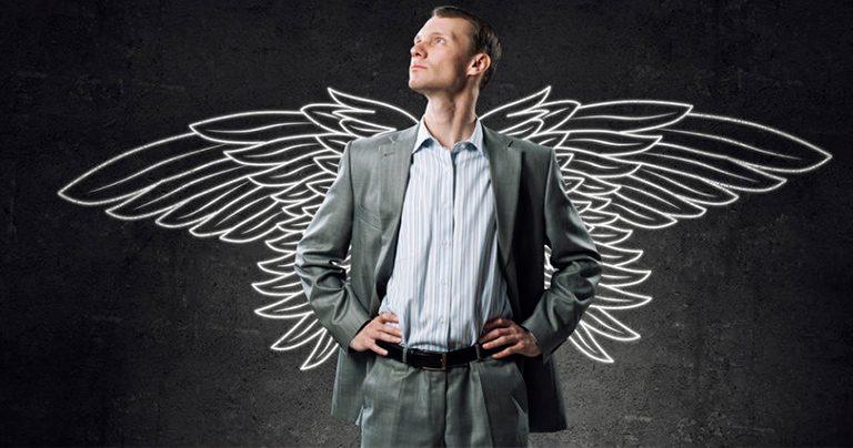 homem com olhar confiante direcionado para cima enquanto apoia as mãos na cintura está a frente de um desenho de asas brancas feitas em um fundo preto