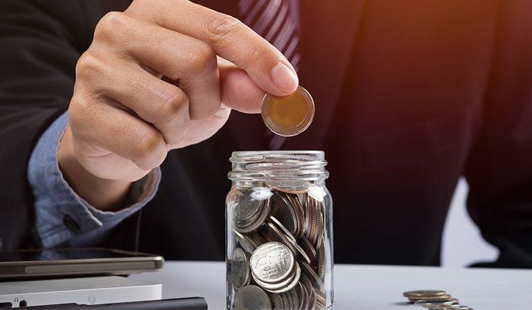 homem de terno colocando moedas dentro de um pote sinalizando o novo limite da DME