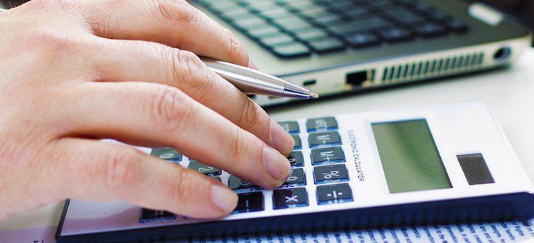 um homem usa a calculadora retratando a importância do cálculo de depreciação