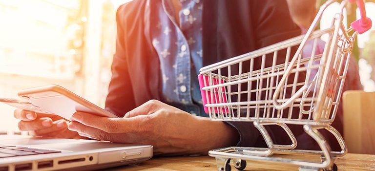 um pequeno carrinho de compras aparece a frente de um homem que observa um papel enquanto digita ao celular representando a base de cálculo do icms