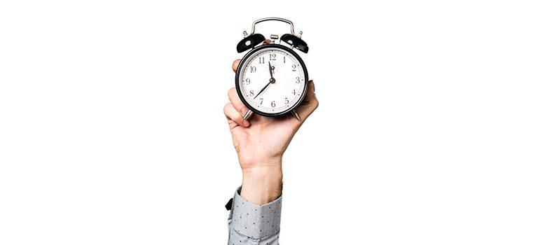mão segura relógio para o alto em fundo branco