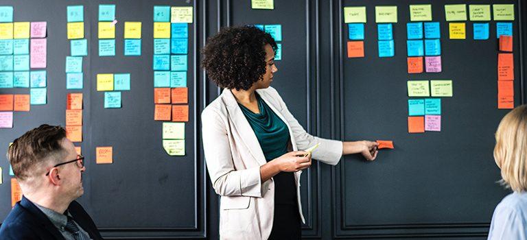 mulher em pé de frente para uma parede preta enquanto cola post its coloridos, atrás dela, dois colegas de trabalho estão sentados e observando