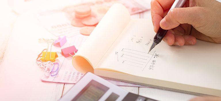 uma mão escrevendo num bloco de notas encima de uma mesa com artigos de papelaria sinaliza o regime de competência e de caixa