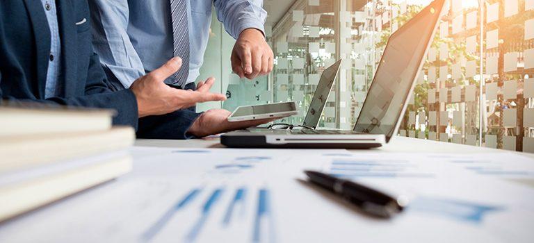 mãos aparecem perto de notebook e planilhas espalhadas pela mesa fazendo contas sobre folha de pagamento